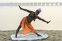 Rome Baba Sadhu practising yoga at sunrise on Ganges riverbank, For Editorial Use Only, Allahabad Kumbh Mela, World's largest religious gathering, Utt...
