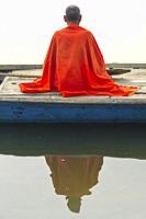 Sadhu with red shawl on a boat on the Ganges river at sunrise, Allahabad Kumbh Mela, World's largest religious gathering, Uttar Pradesh, India.