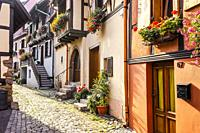 cobblestone lane in medieval village Eguisheim, Alsace, France, houses behind the town wall.