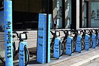 A man smokes a cigarette behind a blue coloured bicycle rental spot in downtown Toronto, Ontario, Canada.