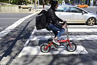 A woman with a hat and backpack rides on a small bicycle through a downtown intersection crosswalk, Toronto, Ontario, Canada.