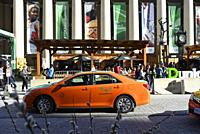 An orange taxicab in front of a temporary, summer-long food and beverage festival at rushhour in front of Union Station, Toronto, Ontario, Canada.