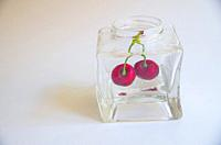 Two cherries in a glass jar.