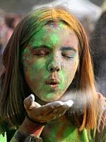 Girl blowing color at Color festival, Krakow, Poland.