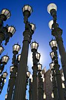 Multiple historic street lights stand in a pattern.