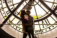 """Lovers embrace in front of the clock at Musee d""""Orsay, a museum in Paris, France, on the Left Bank of the Seine. It is housed in the former Gare d'Ors..."""
