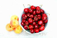 Cherries in a white bowl and apricots on a table