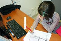 A young girl draws at her mother´s office desk.