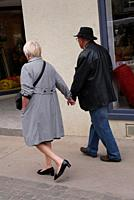 An elderly couple walk hand in hand down a street. Pézenas, France