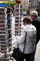 Tourists selecting picture postcards. Pézenas, France