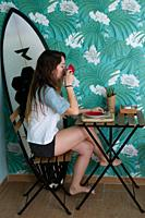 Young woman drinking coffee, in a cafe, next to your surfboard
