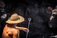 young man with a straw hat on recording images with a Go-pro camera mounted on a stick above tjhe sea