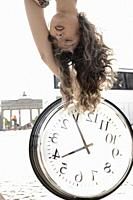 young woman upside down with clock at street next to touristic sight Brandenburger Tor, Brandenburg gate, in Berlin, Germany