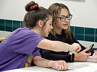 7th Grade Girls Using Smart Phone, Wellsville, New York, USA.