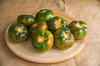 Green tomatoes on wooden dish. Still life.