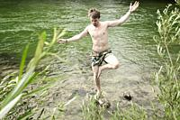 man balancing on stone in river Isar, in Munich, Germany