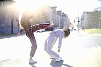 two young women fighting at street, wearing pyjamas, roundhouse kick