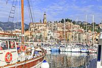 France, Alpes Maritimes, Menton, the Vieux Port with sailboats and the old town dominated by the Saint Michel Archange basilica.