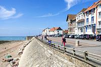 Tourists walking on promenade and shingle beach at Ambleteuse along rocky North Sea coast, Côte d'Opale / Opal Coast, France