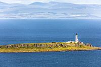 Lighthouse on the island of Pladda on the Firth of Clyde, with a view east to the coast of Ayrshire near West Kilbride, Scotland, UK.