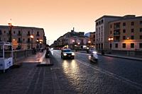 Vittorio Emmanuel bridge, connecting Ortigia and Siracusa at dusk. Dark stones in the pavement glow in the headlights of cars and scooters on a warm s...