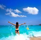 Ibiza beach girl splashing water open arms in Balearic islands.