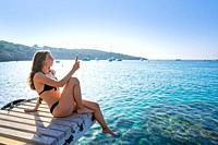 Ibiza girl taking smartphone photos at Portinatx beach pier in Balearic Islands.