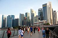 Singapore, Republic of Singapore, Asia - Visitors at the riverfront in Marina Bay with the city skyline of the central business district in the backdr...