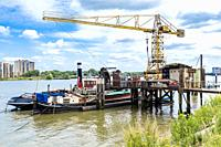Rotterdam, Netherlands. Little, one pier shipyard and warf with crane, installing and maintaining ship's systems, on the banks of Nieuwe Maas River.