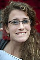 Tilburg, Netherlands. Portrait of a smiling, brunette woman wearing glasses.
