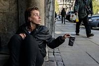 Sofia, Bulgaria. impoverished, young adult Roma woman begging for money in the streets of the Bulgarian capitol, using a carton, disposable coffee cup...
