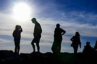 Silhouettes of people against the light at Cape Finisterre, A Coruña, Galicia, Spain