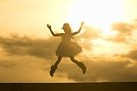 Silhouette of a girl with hat dancing in the sunset