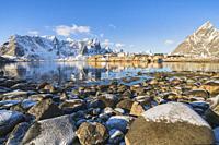 Sariskoy village in winter, with rocky beach in the foreground. Reine, Lofoten district, Nordland county, Northern Norway, Norway.