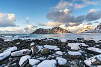 Skagsanden beach in winter, with rocks and snow in the foreground at sunset. Flakstad, Nordland county, Northern Norway, Norway.