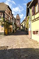 medieval town gate with tower at the Alsace Wine Route, wine village Ammerschwihr, France.