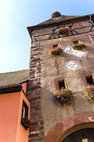 gate tower with flower decoration of Ammerschwihr, Alsace , Wine Route, France.
