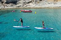 MALLORCA, SPAIN - JUNE 23, 2019: Stand up paddlers on clear turquoise water near the shore on a sunny day on June 23, 2019 in Mallorca, Spain.