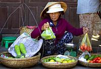 Woman selling vegetables on the fresh food market of Hoi An Old Town, Vietnam, Southeast Asia.
