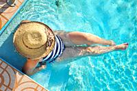 Woman in a hat resting and enjoying a swimming pool.