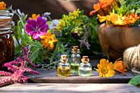 Bottles of essential oil with fresh calendula and other medicinal herbs and flowers.
