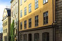 Old architectural style cut stone, brick and stucco building facades with rows of windows, Stockholm, Sweden, Europe.
