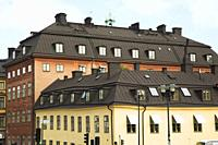 Old beige and burgundy coloured architectural buildings with brown sheet metal roofs rows of windows, Gamla Stan, Stockholm, Sweden, Europe.