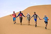group of people rushing down one of the sand dunes at Tinfou, near Tamegroute, Draa River valley, Province of Zagora, Region Draa-Tafilalet, Morocco, ...