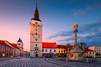 Trnava, Slovakia - April 9, 2019: City tower and Holy Trinity Statue in the main square of Trnava, Slovakia.