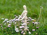Wooden mannequin between flowers on spring time Ecology concept.