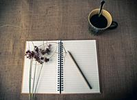 Vintage style. Organized desk with open notebook, a cup of coffee, dry grass, pencils and burlap background.