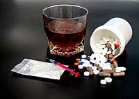 Pills of different sizes, shapes and colors, a glass of whiskey, drugs and syringes Concept of drugs and alcohol.