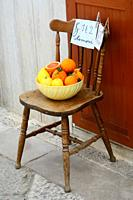 Bowl with fruit on a chair for sale in Bernalda, Basilicata, Italy.
