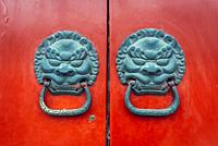 Knockers on a red door of siheyuan courtyard in traditional hutong residential area in Dongcheng district of Beijing, China.
